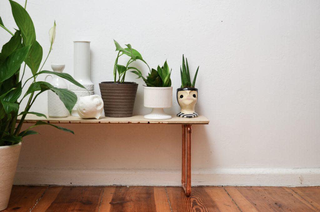 Selbst gemachte Pflanzenbank mit Holzdiele und Kupferrohren